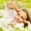 Beautiful female laying on the flower filed — Stock Photo #5387018