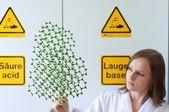 Woman looks into a molecule model — Stockfoto