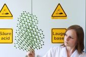 Woman looks into a molecule model — Stock Photo