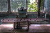 Old abandoned laundry ironing machine in — Stock Photo