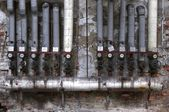 Old pipes with valves and ads — Stock Photo