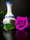 Large rose next to a white decorated vase — Stock Photo