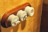Old light switch and plug with wooden base — Stock Photo