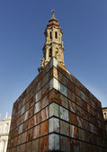 Marble modern building contrasts with an old church in Zaragoza, — Stock Photo
