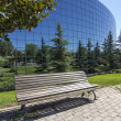 Old wooden bench contrasts with modern glass building — Stock Photo