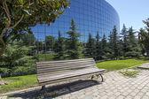 Gammal träbänk kontraster med moderna glasbyggnad — Stockfoto