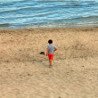 Beach with a small child walking red trousers — Stock Photo