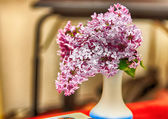 White vase with lilac flowers — Stock Photo