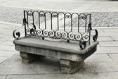 Ancient granite bench seating and wrought iron backing — Stock Photo