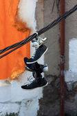 Shoes hanging from a cable on a city street — Stock Photo