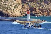 Small fishing boat sailing near the coast in a blue sea — 图库照片