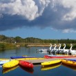 Boats and canoes made of many colors on a quiet lake with blue s — Stock Photo