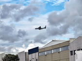 Aereo cargo militare volando basso sopra le case — Foto Stock