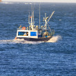 Stock Photo: Small fishing boat sailing near coast in blue sea