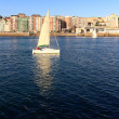 Foto Stock: Small sailboat white sailing in front of city of Santander,