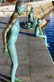 Modern figures in bronze of child jumping into the sea from a pi — Stock Photo