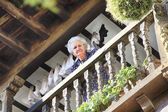 Santillana del Mar, SPAIN Feb 5: old woman observes the street from a typical wooden balcony, Feb 5, 2013 in Santillana del Mar ,Spain. — Stock Photo