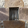 Old window with iron bars in stone wall — Stock Photo