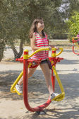 Young Girl using an exercise machine in a park — Stock Photo