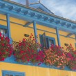 Brightly colored house with balcony full of flowers — Stock Photo