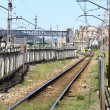 ストック写真: Rail train entering station, with many utility poles