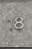 Number eighteen (18) on a wall — Stock Photo