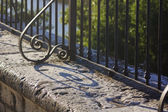 Wrought iron fence with her elongated scraps — Stock Photo