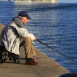 Stock Photo: Older mfishing on shores of sewith cane
