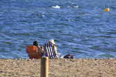 Tourist couple resting against the sea on a beach — Stockfoto