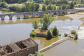 Ruins of warehouse next to a river and a bridge — Stock Photo