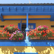 Brightly colored house with balcony full of flowers — Stock Photo #40507201