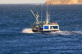 Small fishing boat sailing near the coast in a blue sea — Stock Photo