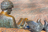 Bronze statue woman sitting reading in a park bench — Stok fotoğraf