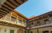 Spanish beautiful old building with white walls and wooden decki — Stock Photo