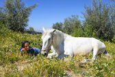 Beautiful white horse with a young woman at his side among the f — Stock Photo