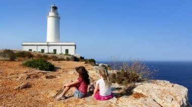 Happy little sisters girls feeling wind in high cliff sea — Stock Video