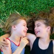 Stock Photo: Sisters kid girls smiling lying on garden grass