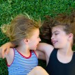 Sisters kid girls smiling lying on garden grass - Stock Photo