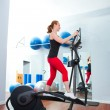 Aerobics cardio training woman on elliptic crosstrainer - Stock Photo