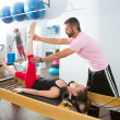Pilates aerobic personal trainer man in cadillac - Stock Photo