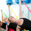 Aerobics pilates women with rubber bands in a row - Стоковая фотография