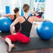 Foto Stock: Stability ball in women Pilates class rear view