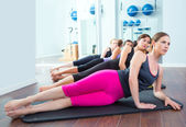 Pilates women group lying on mat with gym instructor — Stok fotoğraf