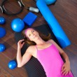 Aerobics woman tired resting lying on mat - Stockfoto