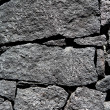 Black lava stone volcanic masonry wall — Stock Photo