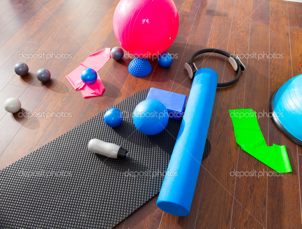 Aerobic Pilates stuff like mat balls roller magic ring rubber bands on wooden floor — Stock Photo #13300311