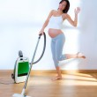 Beautiful pregnant woman retro vacuum housewife — Stock Photo #13477956