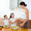 Beautiful pregnant mother with her daughters at kitchen — Stock Photo #13478053