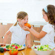 Stock Photo: Beautiful chef sisters at home kitchen preparing salad