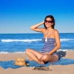 Beautiful pregnant woman sitting on blue beach sand — Stock Photo #13478242